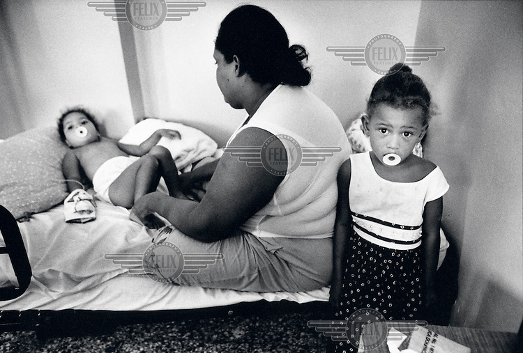 Alicia Gomez (25) sits in hospital with her daughters Margarita (4) and Mariselli (2) while they receive treatment for pneumonia.