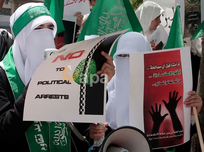 Hamas members of the Palestinian Legislative Council (PLC) take part with Palestinian supporters of the Hamas Islamist movement during a rally calling for the release of Palestinians being held in West Bank and Gaza Strip jails in the West Bank city of Hebron on May 26, 2011.Photo by Najeh Hashlamoun