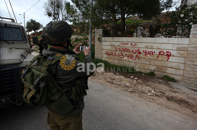 An Israeli soldier take pictures for a wall with hebrow writing following an apparent price tag attack by Jewish settlers in the West Bank village of Deir Jarir, northeast of Ramallah, on February 5, 2013. Suspected Jewish extremists torched a vehicle and scrawled Hebrew graffiti on a nearby wall in the village, Palestinians and Israelis said. Photo by Issam Rimawi