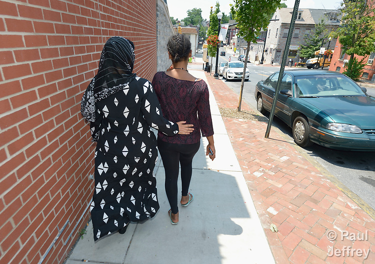 Two refugee women from different cultures walk together as friends along a street in downtown Lancaster, Pennsylvania. The women were participating in a cultural orientation class sponsored by Church World Service.<br /> <br /> Photo by Paul Jeffrey for Church World Service.