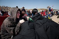 """Searchlight, Nevada, March 28, 2010 - From left, Anthony Eastman, Brittainy McClellan and Alyssa McClellan try to stay warm during the windy first Tea Party Express rally in Searchlight, the hometown of Senate Majority Leader Harry Reid. Levi Russell, the Tea Party Express PIO says, """"Youth voters are more engaged, more in tune, more aware than anybody realizes. They don't always vote, but we want to change that."""" Dubbed the Showdown in Searchlight, the event is located just north of town on private property near Reid's home. The raucous, but peaceful event was expected to draw 5,000 to 10,000 supporters, with actual estimates ranging from 7,000 to 8,000 - though party organizers said the numbers were as high as 13,000. The 20-day tour will wind through the United States ending up in Washington, D.C. on April 15 for a tax day rally. ...."""