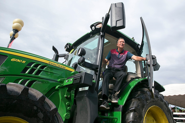UNITED STATES - August 17: Republican presidential candidate and Ohio Governor John Kasich exits a John Deere tractor  after riding it down the concourse at the Iowa State Fair on Tuesday, August 18, 2015 in Des Moines, Iowa. (Photo By Al Drago/CQ Roll Call)