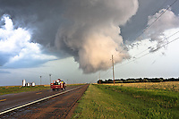Wall cloud hovering over a highway w/ emergency vehicle in La Crosse, KS,  May 25, 2008