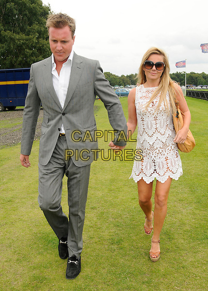 HENRY BECKWITH & GERI HALLIWELL .At the Cartier International Polo, Smith's Lawn, Windsor Great Park, Windsor, England, UK, July 26th 2009..full length couple grey gray suit white shirt lace crochet mini dress beige tan bag shoes brown wedges sheer cut out see through sunglasses holding hands .CAP/CAN.©Can Nguyen/Capital Pictures