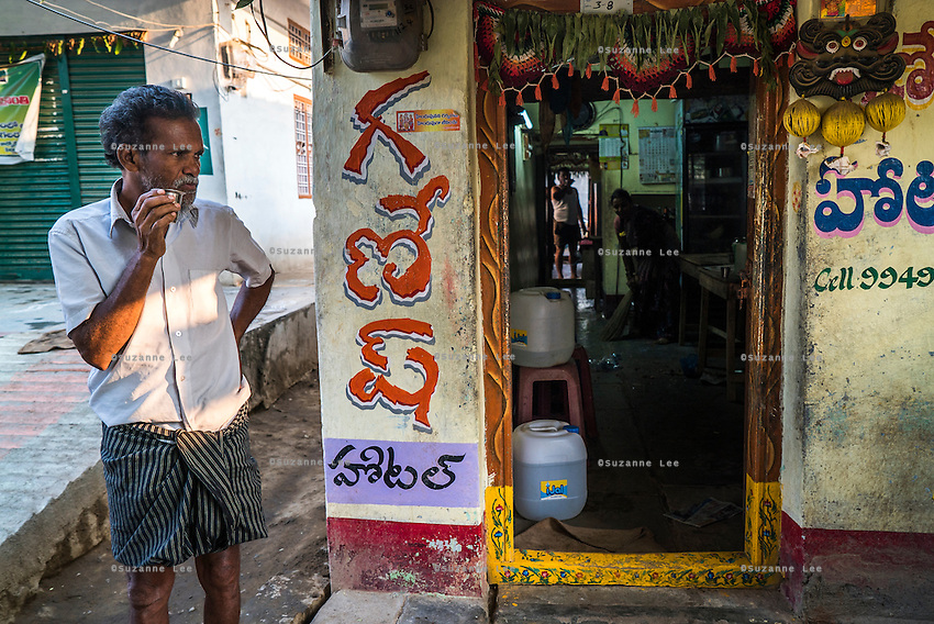 A customer drinks his cup of tea outside Lavanya's food stall in Peddapur, a remote village in Warangal, Telangana, India, on 22nd March 2015. Lavanya buys iJal water and uses it for all her family consumption, and also cooks with it in her stall and serves it for free to customers who come to eat there. She leaves the iJal water cans at the door, showing off to her customers that she uses safe water. Photo by Suzanne Lee/Panos Pictures for Safe Water Network