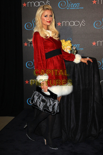 PARIS HILTON .celebrates the launch of her latest fragrance 'Siren' held At Macy's Glendale Galleria, California, USA, .3rd December 2009..full length red christmas santa mrs claus xmas outfit dress white fur fluffy trim black waistband knee high socks shoes  silver platform velvet bag .CAP/ADM/KB.©Kevan Brooks/Admedia/Capital Pictures