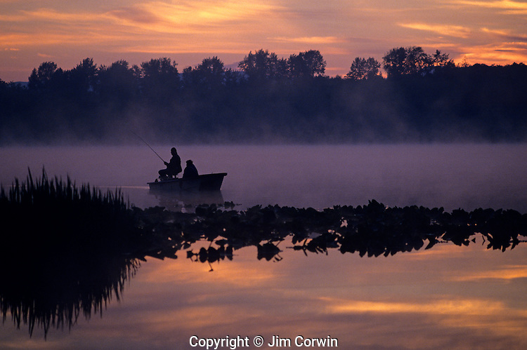 Sunrise at Lake Cassidy in fog with silhouetted fishermen in small rowboat fishing Marysville, Washington State USA