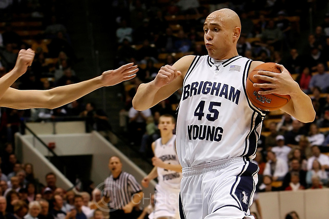 Provo, UT --12/15/07--.Pepperdine's Jason Walberg, #12, gouges the eyes of BYU's Jonathan Tavernari, #45, during the game at the Marriott Center.  No foul was called on the play. Although Tavernari missed the basket immediately following the eye gouge, he did not seem to be injured.  Later in the game, he made back-to-back three-pointers along the right baseline, helping secure BYU's lead.  Tavernari finished the game with 10 points...*******************.BYU plays Pepperdine in men's basketball...Photo by Chris Detrick/The Salt Lake Tribune.frame #_2CD0616