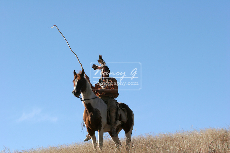 A Native American Indian man siting bareback on a horse riding the prairie of South Dakota