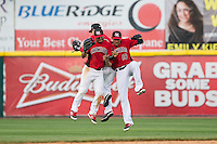 (L-R) Eduard Pinto (2), Jose Cardona (8), and Luke Tendler (18) celebrate their win over the Greensboro Grasshoppers at L.P. Frans Stadium on May 6, 2015 in Hickory, North Carolina.  The Crawdads defeated the Grasshoppers 1-0.  (Brian Westerholt/Four Seam Images)