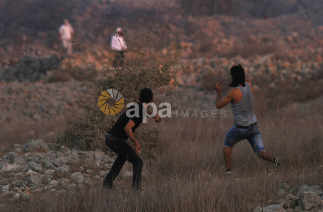 Palestinian protesters hurl stones towards Israeli settlers during clashes in the West Bank village of Burin on October 3, 2015. Sporadic clashes erupted between Palestinians and a dozen settlers from the settlement of Yitzhar, which is known as a bastion of extremists, when the settlers threw stones at Palestinians who responded in the same wa. Photo by Nedal Eshtayah