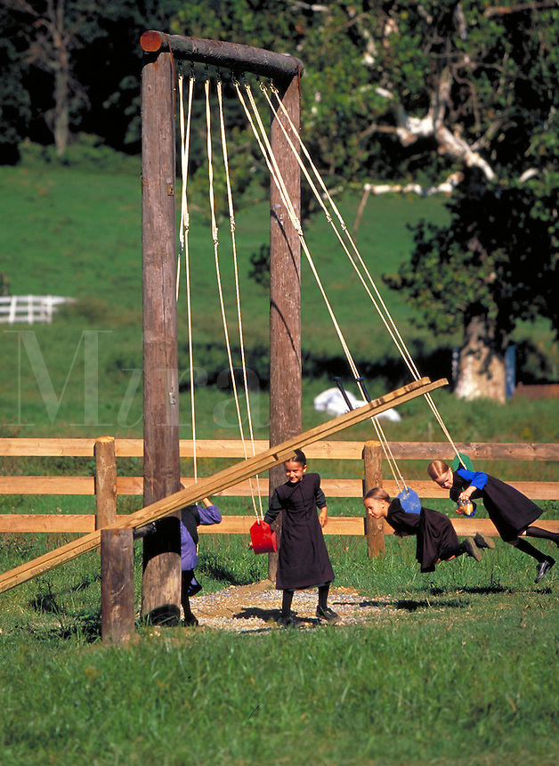 Amish children playing on a wooden swing set. Children. Strasburg Pennsylvania USA Lancaster County.
