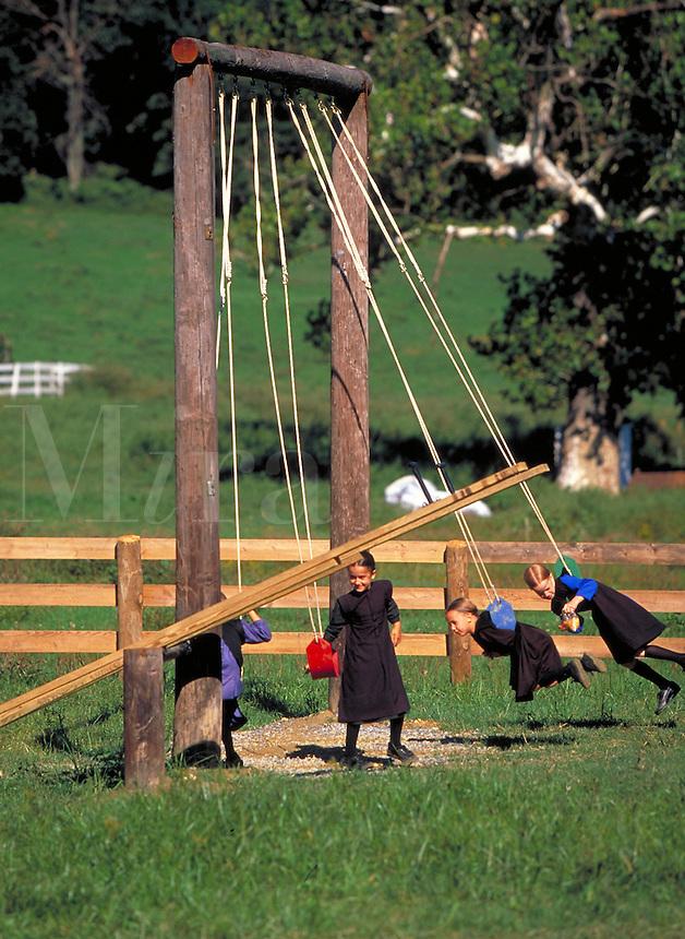 Amish children playing on a wooden swing set. Children. Strasburg Pennsylvania USA Lancaster County.