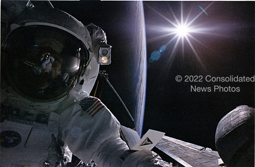 Astronaut Joseph R. Tanner, STS-82 mission specialist, is backdropped against the Earth's limb and a sunburst effect in this 35mm frame exposed by astronaut Gregory J. Harbaugh, his extravehicular activity (EVA) crew mate. Harhaugh's torso is reflected in Tanner's helmet visor. The two were making their second space walk and the fourth one of five for the STS-82 crew, in order to service the Hubble Space Telescope (HST).  A checklist of tasks is attached to Tanner's left arm for quick reference.<br /> Credit: NASA via CNP