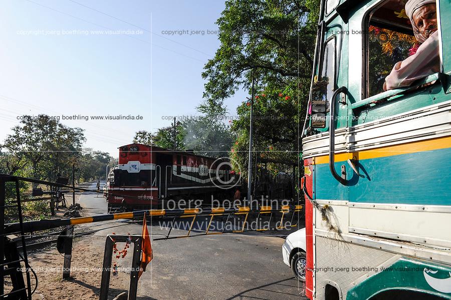INDIA, Madhya Pradesh, Nimad region, Khargone, Railroad Crossing with closed barriers, running train, diesel locomotive