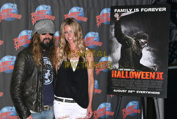 "ROB ZOMBIE & SHERI MOON ZOMBIE .promote the movie ""Halloween II"" by donating memorabilia to Planet Hollywood Times Square, New York, NY, USA, August 18th 2009..half length black leather jacket cap hat beard facial hair husband wife couple poster 2.CAP/LNC/TOM.©LNC/Capital Pictures."