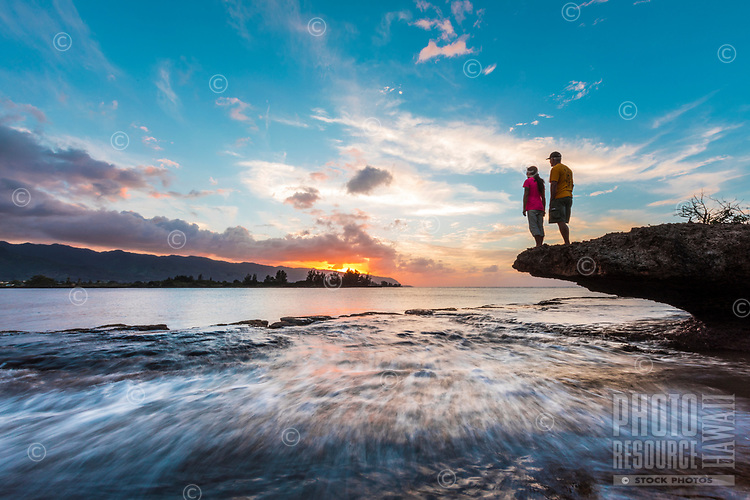 A couple enjoys the sunset and surroundings on the North Shore of O'ahu.