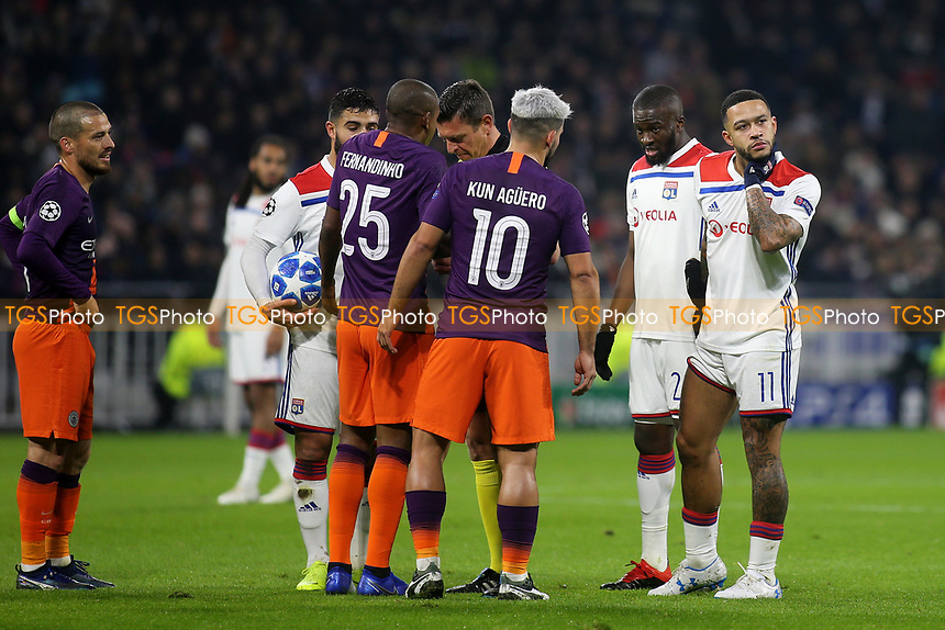 Lyon's Memphis Depay checks that his head is still on his shoulders as Manchester City's Fernandinho is booked during Lyon vs Manchester City, UEFA Champions League Football at Groupama Stadium on 27th November 2018