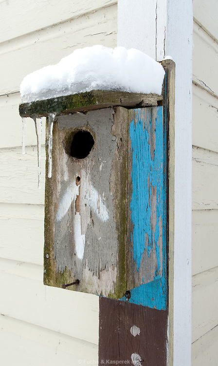Snow sits on a rustic bird house.