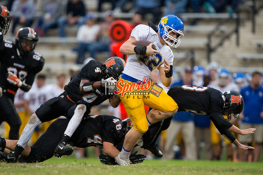 Clayton Horn (42) of the Mount Pleasant Tigers bounces off the hits from Caleb Perkins (23) and Kalan Chapman (4) of the Northwest Cabarrus Trojans during first half action at Trojan Stadium October 1, 2015, in Concord, North Carolina.  The Tigers defeated the Trojans 42-0.  (Brian Westerholt/Sports On Film)