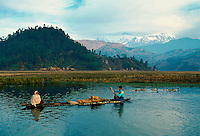Man rowing woman and cargo in foothills of the Himalayas, near Pokhara in Nepal.  Behind is Annapurna range of mountains