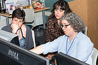 Megan Gall, of Washington, D.C., (right) speaks to Sarah Hugenberger, of Arlington, Mass., (left) and Rosemary Fasselin, of Salt Lake City, Utah, during the Metric Geometry and Gerrymandering Group (MGGG) hackathon at the Data Lab in the Tisch Library at Tufts University in Medford, Massachusetts, USA, on Thurs., Aug. 10, 2017. Gall is a Social Scientist at the national Lawyers' Committee for Civil Rights Under Law. She is working on ways to routinize ecological inference statistics and then visualize that as a way to teach others what ecological inference means and does. Ecological inference is a way of using aggregate data, such as racial or ethic information, to infer what an individual might have done, in this case during a vote. Gall, and others investigating gerrymandering, use ecological inference as a way to identify districts that may have racially polarized voting. Hugenberger is a Masters student in Geographic Information Systems at Salem State University. Fasselin is a GIS coordinator at the Wasatch Front Waste and Recycling District. The two were working on a tool to computationally determine whether a voting district had racially polarized voting during an election. The hackathon is part of the first in a series of Geometry of Redistricting workshops put on by the MGGG. Academics, Geographic Information Systems (GIS) professionals, and legal professionals worked together to build tools useful in analyzing voting district data around the country.