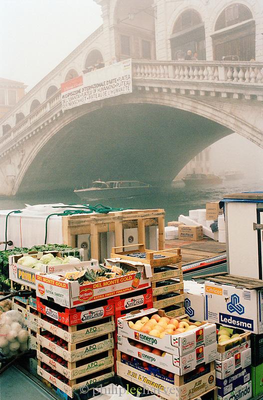 Fresh food produce stacked on a misty morning at the Ponte di Rialto, the Rialto Bridge, Venice, Italy