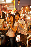 VIETNAM, Hanoi, a sweet young couple sits on their moped eating ice cream on a hot Summer night in downtown Hanoi