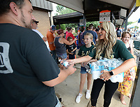 NWA Democrat-Gazette/ANDY SHUPE<br /> Carrie Jernigan (right) and her daughter, Harper, 9, hand out bottles of water Saturday, Aug. 10, 2019, to residents as they wait outside in the heat during the River Valley Kick Start at Alma Middle School. Inspired by her daughter, Harper, Jernigan bought all 1,500 pairs of shoes from a closing Payless Shoe Source in Fort Smith. Her effort national publicity and thousands of dollars in donations, which she used to buy more shoes and school supplies for kids going back to school.