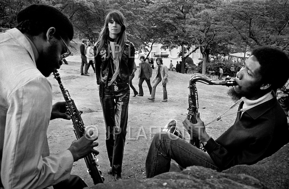 May 1969, Manhattan, New York City, New York State, USA --- French singer Francoise Hardy listens to a saxophonist and a clarinet player in Central Park. --- Image by © JP Laffont