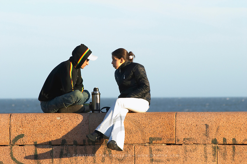 A man and a woman sitting on a red stone facing each other talking conversing and drinking mate herbal tea from a thermos hot water flask. Profile. Sea river in the background. In profile., along the river riverside coast walk Rio de la Plata Ramblas Sur, Gran Bretagna and Republica Argentina Montevideo, Uruguay, South America