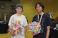 New York, NY, USA - June 22, 2012: Byriah Loper, from Kentucky (left) and Daniel Kwan, from New Jersey, both Origami designers, hold samples of their colorful modular creations at the OrigamiUSA 2012 convention exhibition held at Fashion Institute of Technology in New York City.
