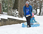 Brennan Hartin of Belleville pulls his daughter Johanna Hartin, 6, in an inflatable tube sled as they walk down McKinley Avenue to East End Park in Belleville on Saturday morning January 12, 2019. People were busy digging out -- and some were having fun -- after a major snowstorm hit the St. Louis metropolitan region. <br /> Photo by Tim Vizer
