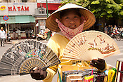 A young woman selling fans as souvenirs to tourists outside of the Ben Thanh Market, Saigon Vietnam.