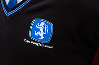 COPY BY TOM BEDFORD<br /> Pictured: Detail on a school uniform of a pupil at Ysgol Penglais School in Aberystwyth, Wales, UK<br /> Re: More than 400 pupils at a comprehensive school in Aberystwyth were given detention on their first day back for breaking school uniform rules.<br /> The uniform was changed at Ysgol Penglais over the summer, following a consultation.<br /> But a number of parents have complained to the school and some 250 have signed a petition saying the punished pupils were &quot;treated unfairly&quot;.<br /> Ceredigion council said a large number of pupils were kept in at break times.<br /> The new uniform was brought in for the start of the new academic year, with the old navy blue pullover and white polo shirt replaced by a grey v-neck jumper, white shirt and a tie. Sixth formers have a similar outfit.<br /> It is compulsory for all pupils in years 7 and 12 to wear the new uniform, with other students being given the rest of the year to buy it.<br /> This was outlined in correspondence sent to all parents over the summer months, which also stipulated what trousers, skirts and shoes would be deemed acceptable.<br /> But the petition said the new rules were not clear enough and that the pupils should not have been punished for their parents' mistakes.<br /> It also said a warning should have been given before the detention.