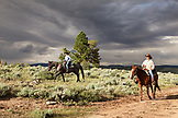USA, Wyoming, Encampment, a man and woman ride horses under a dramatic sky, Abara Ranch