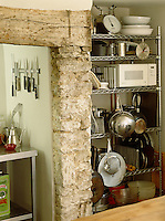 Open metal shelving filled with kitchen untensils and a microwave contribute to the modern functional appearance of this rustic kitchen