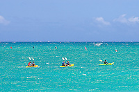 A group of kayakers move across Kailua Bay with flags in the background from a canoe race