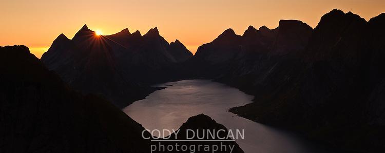 Sunset behind rugged mountain peaks and Kjerkfjord from Reinebringen peak, Reine, Lofoten islands, Norway