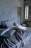 A makeshift bed on a platform at the rear of the stone-built house