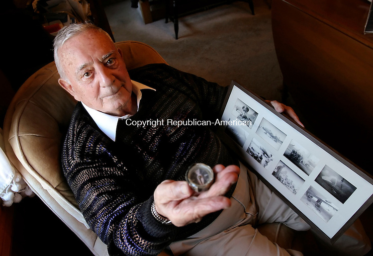 WATERBURY, CT 3 November 2005 -110305BZ01-  Frank Petrillo, a bombardier with the U.S. Army Air Corp 381st Bomb Group, 534th Squadron of the 8th Air Force, poses in the living room of his Waterbury home holding a compass he made while a &quot;guest&quot; (prisoner) of the German Army in Stalag Luft III during WWII.  Petrillo is also holding a framed set of photographs of his B-17 &quot;Hell's Angel&quot; and its crew.  Petrillo was shot down and held as a P.O.W.<br /> Jamison C. Bazinet Republican-American