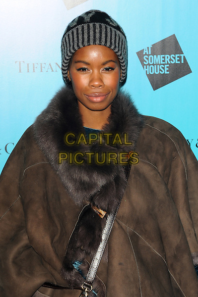 Tolula Adeyemi.Tiffany & Co presents the Winter party celebrating the opening of 'Skate at Somerset House' Ice Rink, London, England..November 21st 2011.half length black  brown poncho grey gray striped stripes fur beanie hat .CAP/CJ.©Chris Joseph/Capital Pictures.