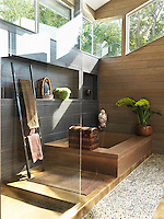 Sunlight floods into the Japanese-style bathroom from a series of picture windows set high up in the walls