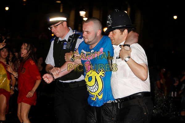 FAN & POLICE.Spanish Football fans celebrate as Spain win the World Cup for the first time in history, Trafalgar Square, Piccadilly, London, England, UK, July 11th 2010..half length fan custody policeman.policemen officer blue t-shirt .CAP/MAR.© Martin Harris/Capital Pictures.