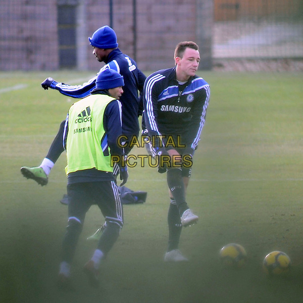 JOHN TERRY.Training at the Chelsea Football Training grounds, Cobham, Surrey, England..February 1st, 2010.full length footballer sport soccer uniform kit black blue shorts top hand pulling up adjusting gloves socks bending leaning .CAP/MUR.©Murphy/Capital Pictures