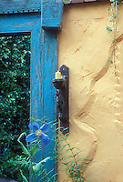 Candle sconce outdoors in the garden on yellow wall with blue doorway, Meconopsis blue flower in bloom