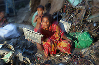 In the village of Sangrampur, a woman sorts e-waste as her child stands nearby, collected for recycling and reselling in nearby Kolkata, India. November, 2013