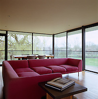 A large pink L-shaped sofa looks out onto the surrounding landscape through the glass walls in this open-plan living/dining room