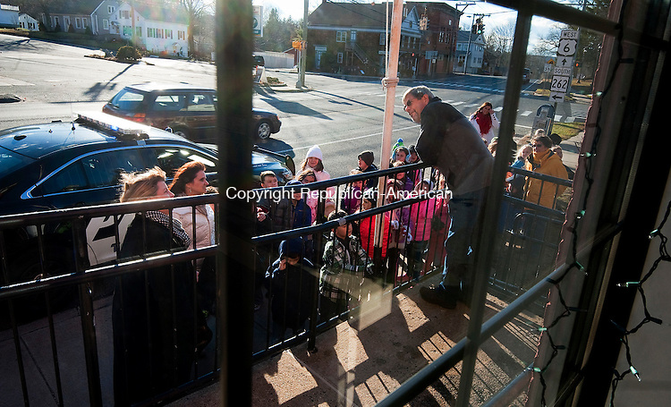 PLYMOUTH, CT--- -120315JS03--Brian Peterson, Postmaster at the Plymouth Post Office, greet first grade student from Plymouth Center School during their annual visit to the Plymouth Post Office to drop off their letters to Santa on Thursday. The children also received a tour of the post office and a gift bag. <br /> Jim Shannon Republican-American