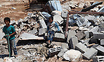 Palestinian children inspect the remains of their family's makeshift home, which was destroyed by the Israeli army in the West Bank village of Aqaba in the northern Jordan Valley, Thursday, July 3,2014. Palestinian security sources said the Israeli army destroyed at least eight makeshift homes which the army said were illegally built in the area. Photo by Shadi Hatem